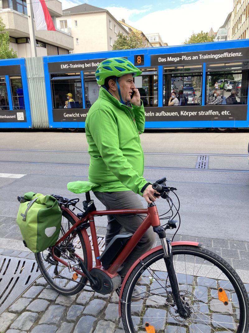 Direktkandidat Boris Mijatovic am Telefon mit Fahrrad in Kassel, August 2021